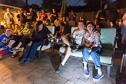 June 11, 2017 - Merrick, New York, United States - 'American Grit' TV contestant CHRIS EDOM (at left, wearing white GOT GRIT? T-shirt), 48, sits with his wife, JOAN EDOM, of Merrick, as they host backyard Viewing Party for Season 2 premiere. Edom family relatives and neighbors watched Episode 1 of FOX network reality television series that Sunday night outdoors. Edom was last of 16 contestants picked for a team. (Credit Image: © Ann Parry via ZUMA Wire)