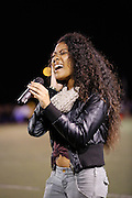 Milpitas High School sophomore Jacinda Miminfield sings the National Anthem before the kickoff during the homecoming game against Saratoga at Milpitas High School in Milpitas, California, on October 11, 2013.  Milpitas beat Saratoga 54-14. (Stan Olszewski/SOSKIphoto)
