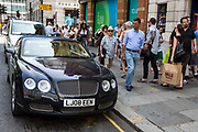 A passing pedestrian admires a Bentley car parked on a single yellow line on King's Road, Chelsea,  London, United Kingdom. King's Road is a affluent area of London popular for upmarket shopping and leading restaurants.