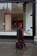 A shopper walks past a window display that is part of a design theme called 'State of the Arts', at the Selfridges department store on Oxford Street, on 4th March 2019, in London England. State of the Arts is a gallery of works by nine crtically-acclaimed artists in Selfridges windows to celebrate the power of public art. Each of the artists are involved in creating a site-specific artwork at one of the new Elizabeth line stations as part of the Crossrail Art Programme.