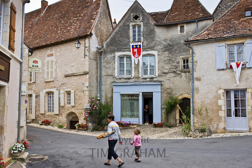 Woman carrying French baguette bread stick walks with child at Angles Sur L'Anglin, Vienne, Poitou-Charantes, France