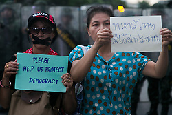 © Licensed to London News Pictures. 26/05/2014. Two anti-coup protestors stand in front of military holding anti-coup signs following a Anti-Coup protest in Bangkok Thailand. Today Thailand's King formally approved Thai army chief General Prayut Chan-O-Cha as head of the nation's new military junta.  Photo credit : Asanka Brendon Ratnayake/LNP