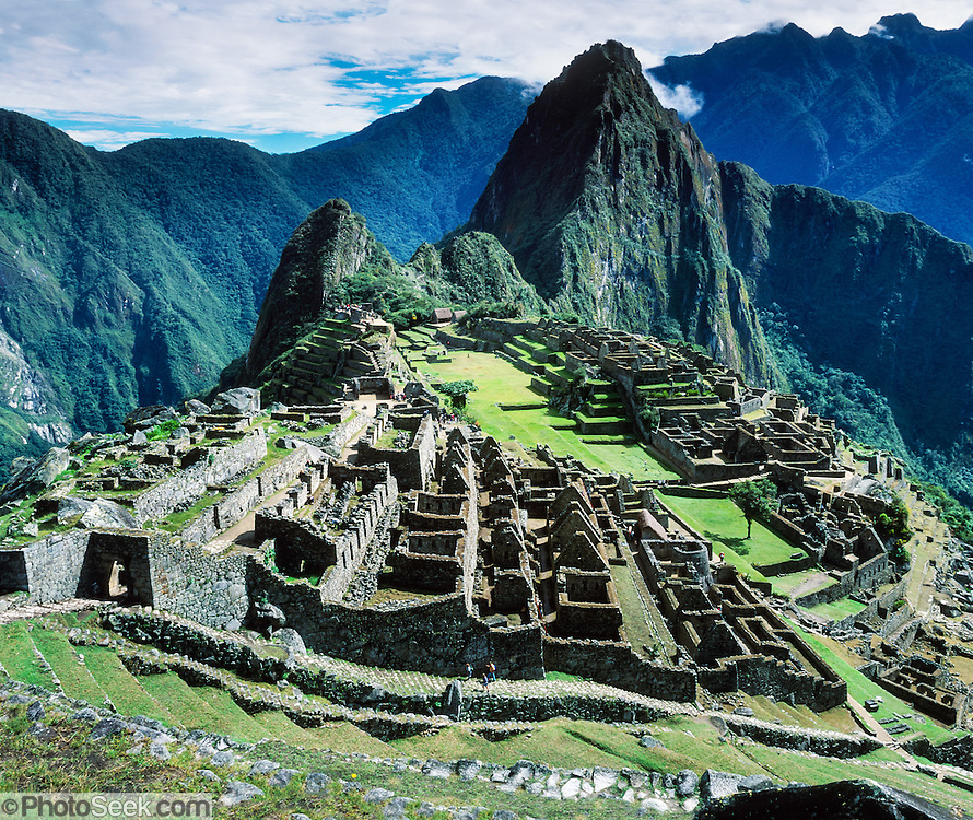 """Machu Picchu is a magnificent Inca archeological site in the Cordillera Vilcabamba, Andes mountains, Peru, South America. A long stairway climbs along Inca walls. Machu Picchu was built around 1450 AD as an estate for the Inca emperor Pachacuti (14381472). Spaniards passed in the river valley below but never discovered Machu Picchu during their conquest of the Incas 1532-1572. The outside world was unaware of the """"Lost City of the Incas"""" until revealed by American historian Hiram Bingham in 1911. Machu Picchu perches at 2430 meters elevation (7970 feet) on a well defended ridge 450 meters (1480 ft) above a loop of the Urubamba/Vilcanota River ( Sacred Valley of the Incas). UNESCO honored the Historic Sanctuary of Machu Picchu on the World Heritage List in 1983.  Panorama was stitched from 3 overlapping photos. Published in 2009 on Swedish trekking company site www.adventurelovers.se."""