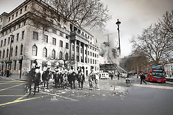 © Licensed to London News Pictures. 25/03/2020. London, UK. In this combined image mounted police wait outside South Africa House on Trafalgar Square during the London poll tax riots on March 31st 1990 overlaid on the same location today. The protest on the last day of March in 1990 started peacefully when thousands gathered in a south London park to demonstrate against Margaret Thatcher's Government's introduction of the Community Charge - commonly known as the poll tax. Marchers walked to Whitehall and Trafalgar Square where violence broke out with the trouble spreading up through Charring Cross Road and on to the West End. Police estimated that 200,000 people had joined the protest and 339 were arrested. The hated tax was eventually replaced by the Council Tax under John Major's government in 1992.  Photo credit: Peter Macdiarmid/LNP