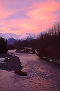 Alaska.  Glacier Creek in the Chugach National Forest , flows down Glacier Valley and past the town ship of Girdwood in winter.   Alpenglow on the snowy mountains.