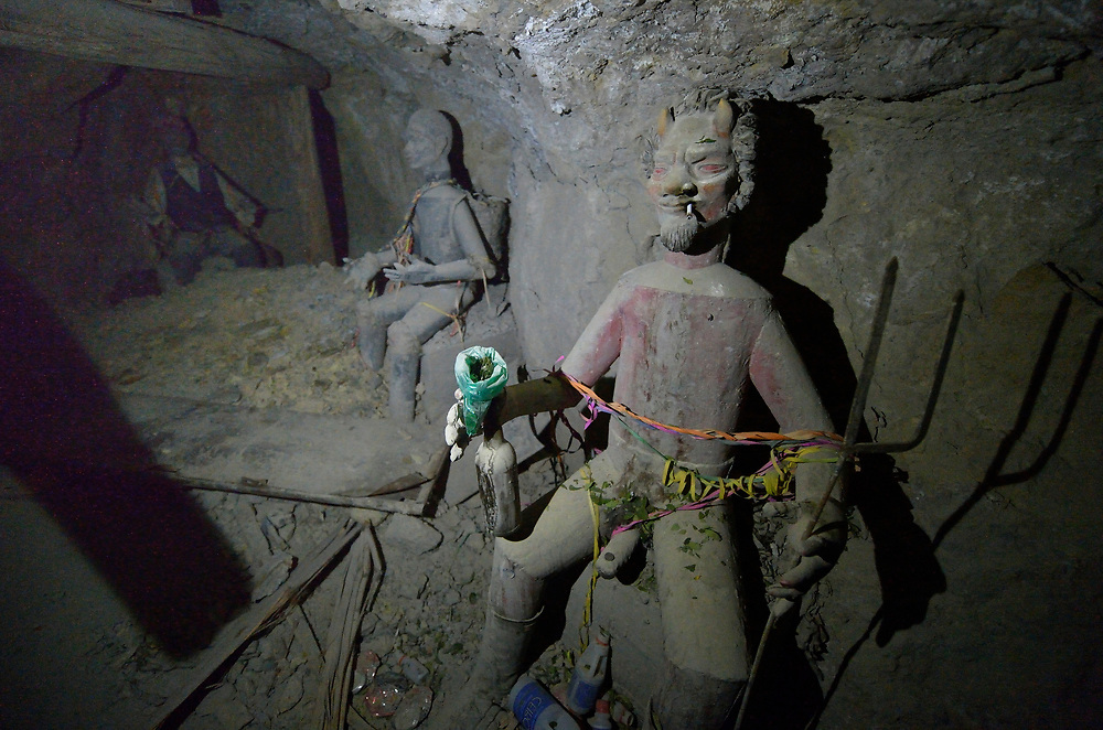 """Old statues of """"El Tio""""  inside a mine in Potosi, Bolivia. El Tio (the Uncle) is considered by most miners here to be lord of the underworld. Miners bring offerings such as cigarettes, coca leaves, and alcohol for the statues, believing that if El Tio is not fed, he will take matters into his own hands. Above ground, most miners are Christians.<br /> <br /> In this mine, these old statues have been placed in a side tunnel, leaving one """"active""""  El Tio near the main entrance."""