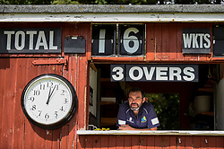 © Licensed to London News Pictures. 11/07/2020. CHORLEYWOOD, UK.  Steve, the solo scorekeeper, watches members of Chorleywood Cricket Club in their first friendly match on the day that the UK government relaxed coronavirus pandemic lockdown restrictions for a several outdoor activities.  Usually, there are two scorekeepers, but due maintain social distancing needs, only one can occupy the booth.  The amateur club have been playing matches on The Common at Chorleywood in Hertfordshire for nearly 200 years.  Photo credit: Stephen Chung/LNP