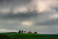 Ominous, stormy clouds above the Chapel of Vitaleta in Val d'Orcia, Tuscany, Italy. The Chapel of the Madonna od Vitaleta is a rural small church placed atop a hill in the country side between Pienza and San Quirico d'Orcia. Taken on a windy and rainy early morning at the beginning of May. The threatening sky makes adds a lot of mood to such an enchanted small rural scene.
