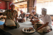 Young Balinese men sit down to enjoy coffee, snack and a cigarette during gathering at Ulun Danu Batur temple - an important social and religious center of the area.