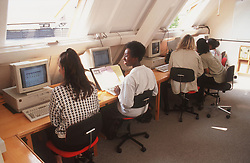 Group of women sitting at desk using computers during adult education computer course,