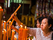 27 SEPTEMBER 2014 - BANGKOK, THAILAND: Women light prayer candles during the celebration of the Vegetarian Festival at the Chow Su Kong Shrine in Talat Noi, a Chinese enclave in Bangkok. The Vegetarian Festival is celebrated throughout Thailand. It is the Thai version of the The Nine Emperor Gods Festival, a nine-day Taoist celebration beginning on the eve of 9th lunar month of the Chinese calendar. During a period of nine days, those who are participating in the festival dress all in white and abstain from eating meat, poultry, seafood, and dairy products. Vendors and proprietors of restaurants indicate that vegetarian food is for sale by putting a yellow flag out with Thai characters for meatless written on it in red.    PHOTO BY JACK KURTZ