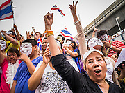 """02 JUNE 2013 - BANGKOK, THAILAND:  Anti-government protesters sing the King's Anthem during a protest against the incumbent government in Bangkok. The so called White Mask protesters are strong supporters of the Thai monarchy. About 300 people wearing the Guy Fawkes mask popularized by the movie """"V for Vendetta"""" and Anonymous, the hackers' group, marched through central Bangkok Sunday demanding the resignation of Prime Minister Yingluck Shinawatra. They claim that Yingluck is acting as a puppet for her brother, former Prime Minister Thaksin Shinawatra, who was deposed by a military coup in 2006 and now lives in exile in Dubai.    PHOTO BY JACK KURTZ"""