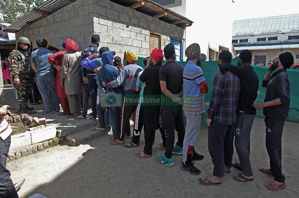 April 29, 2019 - Srinagar, Kashmir, India - People stand in a queue to cast their votes outside the polling station during the second leg of the three-phased voting schedule for the Lok Sabha seat fourth phase of the election in south Kashmir's Kulgam. India's general election which began on 11 April will continue till 19 May 2019 to constitute the 17th Lok Sabha. The counting of votes will be conducted on 23 May, and on the same day the results will be declared. (Credit Image: © Faisal Khan/NurPhoto via ZUMA Press)