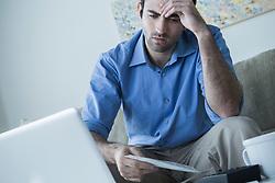 Worried man with hand on head holding bills (Credit Image: © Image Source/ZUMAPRESS.com)
