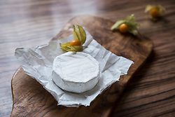 Close-up of white cheese and gooseberry on chopping board, Germany