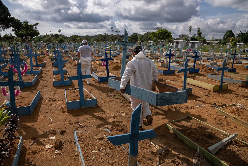 """Staff at Nossa Senhora Aparecida public cemetery prepare to place a blue grave marker called """"Castilhos"""" for people who died of Covid March 30, 2021 in Manaus, Brazil. Brazilian residences are receiving the CoronaVac vaccine, also known as the Sinovac COVID-19 vaccine. CoronaVac is an inactivated virus COVID-19 vaccine developed by the Chinese company Sinovac Biotech and has been in Brazil's Phase III clinical trials. Photo Ken Cedeno"""