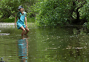 During a class field trip to study life along the river, a fifth grader dances in the shallow water.