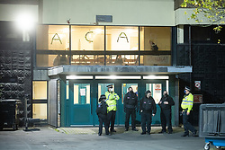© Licensed to London News Pictures. 12/11/2020. Manchester, UK. Police and private security in front of the occupied Owens Park Tower at the University of Manchester's Owens Park campus this evening (12th November 2020) . Students have taken part in a demonstration at the site in support of those who have occupied Owens Park Tower as part of a rent strike at the University . Students object to rent payments for reduced facilities , the University's erection of fencing around the campus and what they describe as the UoM's failure to provide adequate mental health and wider support . Photo credit: Joel Goodman/LNP