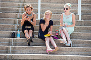 © Licensed to London News Pictures. 31/07/2014. Chichester, UK. Women sit and wait for the racing to begin. Ladies Day at Glorious Goodwood at Goodwood racecourse in Chichester today 31/07/14. Photo credit : Stephen Simpson/LNP