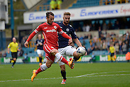 Adam Le Fondre of Cardiff City attempts to chip David Forde of Millwall while Mark Beevers of Millwall is chasing but he shoots over the crossbar when he should have scored. . Skybet football league championship match , Millwall v Cardiff city at the Den in Millwall, London on Saturday 25th October 2014.<br /> pic by John Patrick Fletcher, Andrew Orchard sports photography.