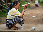 """20 JUNE 2016 - DON KHONE, CHAMPASAK, LAOS: A woman prays while she waits for monks from Wat Khone Nua on their morning alms' rounds, called the """"tak bat"""" in Don Khone village on Don Khone Island. Don Khone Island, one of the larger islands in the 4,000 Islands chain on the Mekong River in southern Laos. The island has become a backpacker hot spot, there are lots of guest houses and small restaurants on the north end of the island.     PHOTO BY JACK KURTZ"""