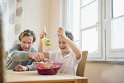 Father and son preparing salad at table