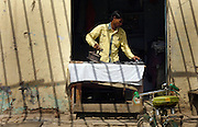 Man ironing outside his shop in Agra, India