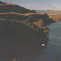 1. When was this photo taken?<br /> <br /> 1982<br /> <br /> 2. Where was this photo taken?<br /> <br /> Spirit Lake, Mt. St. Helens<br /> <br /> 3. Who took this photo?<br /> <br /> Julie Fowells<br /> <br /> 4. What are we looking at here?<br /> <br /> Two years after the eruption of Mt. St. Helens the landscape seemed frozen in time; it was eery how little had changed since the ash settled. This must be what remained of Spirit Lake. You can almost see the windows of the train I shot this through..<br /> <br /> 5. How does this old photo make you feel?<br /> <br /> Thrilled to find a surprisingly well preserved record from that time in my life, heartbroken that I don't remember it better, and devastated my papa isn't alive to see these pictures.<br /> <br /> 6. Is this what you expected to see?<br /> <br /> Every once in a while I've wondered what happened to this, my first ever roll of 35mm. Definitely wouldn't have predicted I'd find it 35 years later, still in the canister, tumbling around in a (lead x-ray proof!) bag of unexposed Kodachrome.<br /> <br /> 7. What kind of memories does this photo bring back?<br /> <br /> Papa bought this camera for me: a Pentax Super Program, which was not only my first 35mm, but sounded very, well... super. I was heading out to spend a year in the Philippines a few weeks later, and felt decidedly grown up.<br /> <br /> Later that week we took a steam train up to the recently transformed Mt. St. Helens, mostly just because my pa really loved old trains. Pretty sure I feigned boredom - the significance of the altered landscape was lost on me - but was privately bursting with pride to be nonchalantly wielding a tool so befitting my worldly sophistication. I remember thinking - hoping - Papa was equally proud of me. <br /> <br /> In retrospect, he probably was.<br /> <br /> 8. How do you think others will respond to this photo?<br /> <br /> Without any context it just looks like a vaguely eery lake. Hard to imaging this landscape e