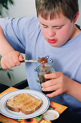 Teenage boy with Downs Syndrome sitting at breakfast table in front of slice of toast using knife to remove marmalade from jar,