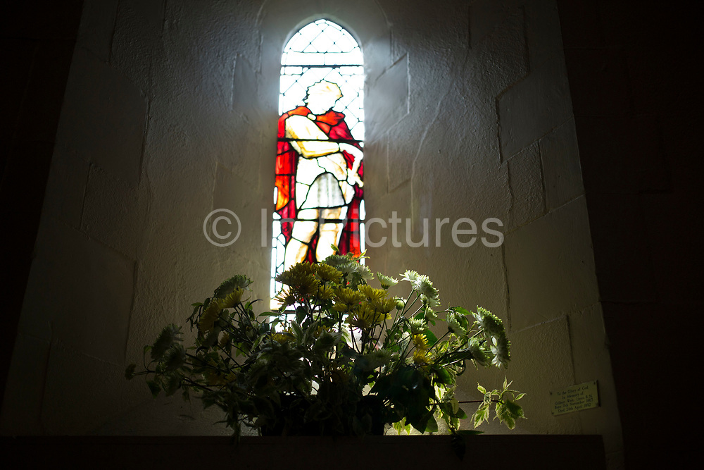 Stained glass window interior viw with flowers in St Bartholomew church in Wanborough, Surrey, UK. Originally a Saxon church, it was rebuilt in the 12th century and is a beautiful and simple chapel originally built for the monks of Waverley Abbey. It now serves the rural parish of Wanborough, as part of the United Parish of Seale, Puttenham and Wanborough.