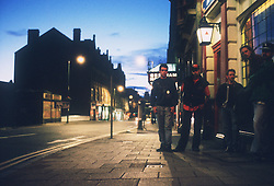 Group of teenage boys standing in street outside pub at night,