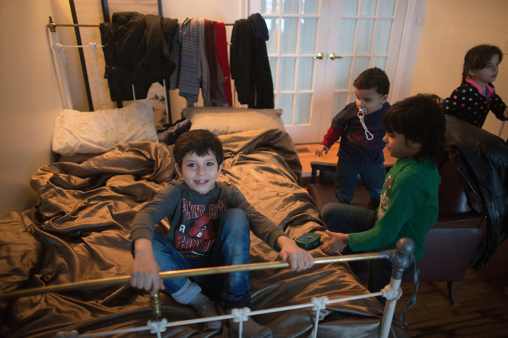 Syrian refugee Madjid Al Jasem sits on a bed with his brothers and sisters inside their temporary home in Picton, Ontario, Canada, Wednesday January 20, 2016.   (Mark Blinch for the BBC)