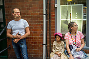 A man with a flamboyant moustache stands with a woman and her child at the African street style Festival, Hackney, London, United Kingdom.