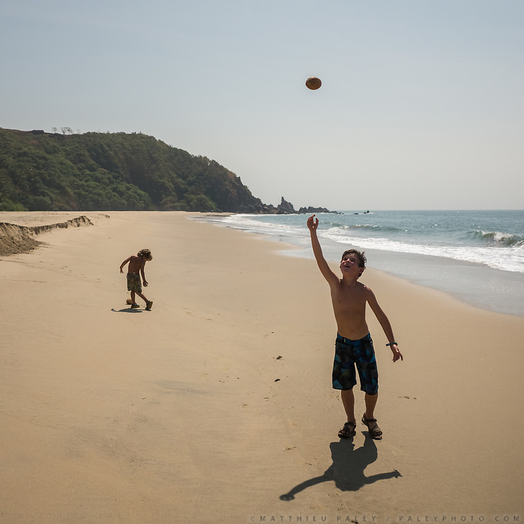 Two brothers walk on an empty beach. Older brother throws a coconut in the air.
