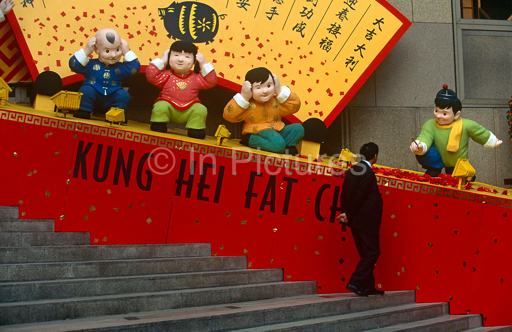 The Chinese words Kung Hei Fat Choi or Happy New Year with cartoon characters outside Bank of China building, Hong Kong. A local businessman stops to seemingly talk with one of the boy characters that appear to be looking straight at the man, while pointing a wand to wish him well. Chinese New Year is the longest and most important festivity in the Chinese Lunisolar Calendar. The origin of Chinese New Year is itself centuries old and gains significance because of several myths and traditions.