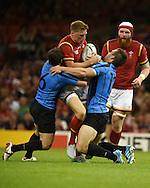 Rhys Priestland of Wales © is stopped by a tackle from Uruguay's Juan Gaminara (l) and Andres Vilaseca ®.  Rugby World Cup 2015 pool A match, Wales v Uruguay at the Millennium Stadium in Cardiff, South Wales  on Sunday 20th September 2015.<br /> pic by  Andrew Orchard, Andrew Orchard sports photography.
