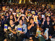 05 DECEMBER 2016 - BANGKOK, THAILAND: People sit on the deck of Bhumibol Bridge and wait for a ceremony honoring the late king to start. Tens of thousands of Thais gathered on Bhumibol Bridge in Bangkok Monday to mourn the death of Bhumibol Adulyadej, the Late King of Thailand. The King died on Oct 13 after a lengthy hospitalization. December 5 is his birthday and a national holiday in Thailand. The bridge is named after the late King, who authorized its construction. 999 Buddhist monks participated in a special merit making ceremony on the bridge.       PHOTO BY JACK KURTZ
