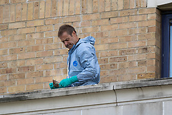 © Licensed to London News Pictures. 05/07/2020. London, UK. A forensics officer holds a blood stained piece of glass as he works on a balcony at the Holiday Inn on Bugsby's Way in Greenwich. Police were called to the Holiday Inn at 10:02hrs this morning to a report of a woman stabbed. Police Officers and London Ambulance Service attended and a woman was found suffering serious injuries and was declared dead at the scene. While attending the incident, a man believed to be known to the woman, fell from height. He was taken to hospital, where he remains under the guard of officers. His condition is being treated as life-threatening. Photo credit: George Cracknell Wright/LNP