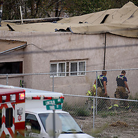 Firefighters walk around a house where a reported gas explosion collapsed the roof near Lincoln Avenue and Third Street in Gallup Wednesday.