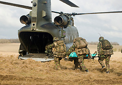 4 Mech Bde taking part in the Mission Specific Training on Salisbury Plain Training Area before deployment to Helmand Province Afghanistan.  The simulated battle casualty from the Royal Dragoon Guards is stretchered onto an RAF Chinook helicopter for evacuation  9 Feb 2010