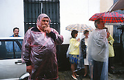 """Rains stops play. Bullfight called off because of the rain. Visitors dressed in flamenco dress covered in plastic raincoats in these rare heavy springtime downpours. Bullfighting in Sevilla's famous bullring """"La Real Maestranza"""" is a significant part of the Feria de Abril..The Feria de abril de Sevilla, """"Seville April Fair"""" dates back to 1847. During the 1920s, the feria reached its peak and became the spectacle that it is today. It is held in the Andalusian capital of Seville in Spain. The fair generally begins two weeks after the Semana Santa, Easter Holy Week. The fair officially begins at midnight on Monday, and runs six days, ending on the following Sunday. Each day the fiesta begins with the parade of carriages and riders, at midday, carrying Seville's citizens to the bullring, La Real Maestranza...For the duration of the fair, the fairgrounds and a vast area on the far bank of the Guadalquivir River are covered in rows of casetas (individual decorated marquee tents which are temporarily built on the fairground). Some of these casetas belong to the prominent families of Seville, some to groups of friends, clubs, trade associations or political parties. From around nine at night until six or seven the following morning, at first in the streets and later only within each caseta, crowds of people party and dance Sevillanas, traditional Flamenco dances, Sevillan style drinking Jerez sherry, or Manzanilla wine, and eating tapas. .."""
