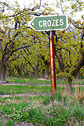 A rusty old road sign pointing the way towards Crozes Hermitage and fruit trees in the background. Crozes Hermitage, Drome, Drôme, France, Europe