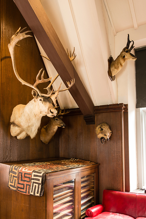 The gallery of The Explorers Club includes displays of ethnologic artifacts and taxidermy. In the cabinet is the mammoth original edition of the Déscription de L'Egypte, published from 1809-1829.
