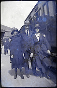 young adult man posing with two girl friends next to train wagon 1900s Europe France
