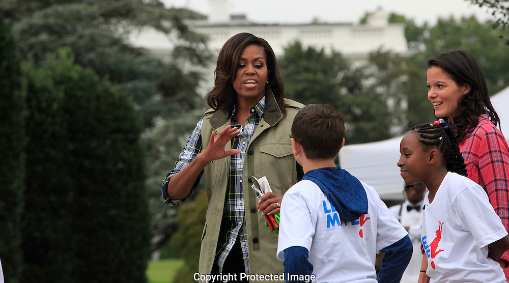 First Lady Michelle Obama works in the  White House Kitchen Garden on the South lawn of the White House.  The lady on the left is  Debra Eschmeyer, the executive Director of Let's Move. Photo by Dennis Brack