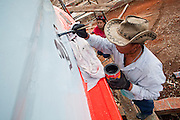 Sept. 24, 2009 -- PATTANI, THAILAND: While his wife, LAONDAO TRACHOWANICH watches him, THAN TRACHOWANICH, 52 years old, paints registration numbers on the side of a fishing boat being rebuilt in Siriudom Shipyards in Pattani, Thailand. Fishing is the main industry in Pattani, one of just three Thai provinces with a Muslim majority. Thousands of people, mostly Buddhist Thais and Burmese Buddhist immigrants, are employed in the fishing industry, either crewing ships, working in processing plants or working in the ship building and refreshing yards.   Photo By Jack Kurtz