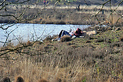 Nederland, Overasselt, 26-3-2020 In het natuurgebied de Hatertse Vennen bij Nijmegen ligt een jong stel bij het water. Door de opgelegde social distancing vanwege het coronavirus houdt iedereen goed afstand van elkaar. Het is niet erg druk en dat gaat goed . Het gebied is enkele jaren geleden door staatsbosbeheer uitgedund om de grondwaterstand te verhogen en de vennen en hei nieuw leven in te blazen. Foto: Flip Franssen