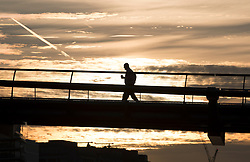 © Licensed to London News Pictures. 13/09/2016. London, UK. A man walks across the Millennium bridge on the River Thames at sunrise. Another warm sunny day is expected with hot temperatures predicted in the south east.Photo credit: Peter Macdiarmid/LNP
