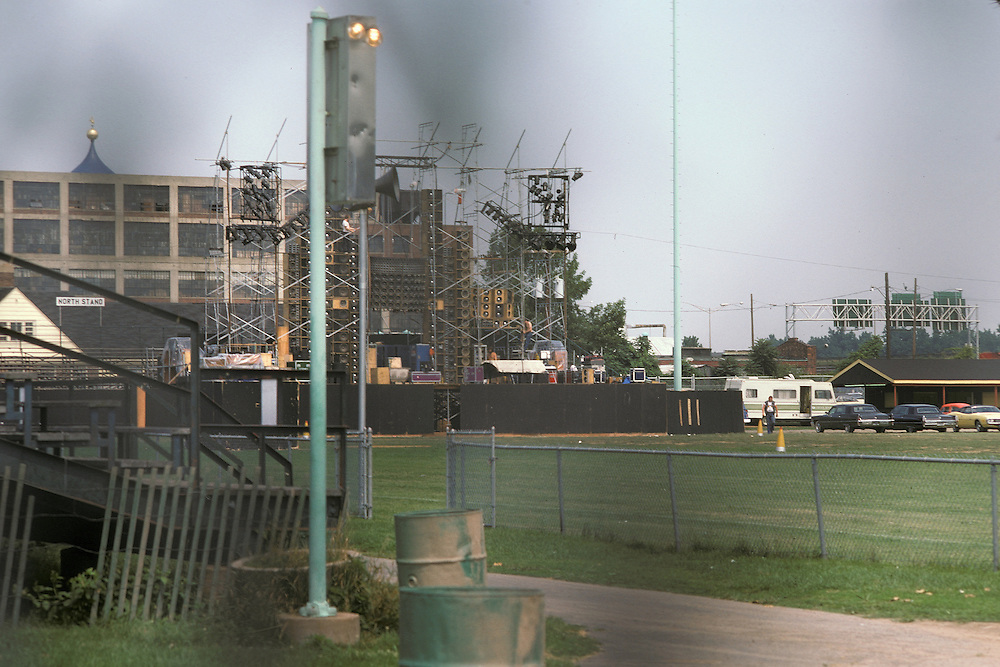 Crews setting up in an Empty Dillon Stadium the Wall of Sound before the Grateful Dead Play Live in Hartford, CT on 31 July 1974. Shot early in the afternoon, before the wind protection scrim was hung and looking through a chain link fence, thus the dark areas in the frame.