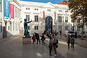 Tourists kissing outside the museum of Sao Roque in Sao Roque Square on the 29th of October 2019  in Lisbon, Portugal. In the background is a statue of Father António Vieira next to the Church of Sao Roque, Lisbon, Portugal.
